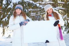 Winter. Young women with blank banner. Royalty Free Stock Photography