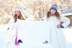 Winter. Young women with blank banner. Royalty Free Stock Photos