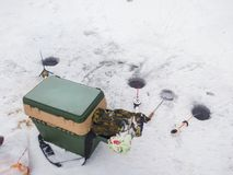 Winterangeln mit Abstreicheisen und kleine Fische auf dem Eis nahe Fischenlöchern und Fischer ` s Reihe auf dem Eis Lizenzfreie Stockbilder