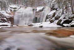 Winteransicht über schneebedeckte Flusssteine zur Kaskade des Wasserfalls Gewellter Wasserspiegel Strom in Tiefkühl Stockfotografie