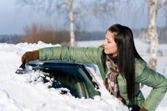 Winterauto - Frau löschen Schnee von der Frontscheibe lizenzfreies stockbild