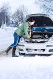 Winterautozusammenbruch - Frauenreparaturmotor stockfoto