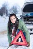 Winterautozusammenbruch - warnendes Dreieck der Frau stockbild