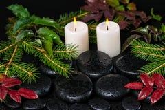 Winterbadekurortkonzept von Zenbasaltsteinen mit Tropfen, Kerzen und Stockfotografie