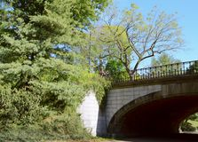 Winterdale Arch in Central Park, New York City. Surrounded by tall trees and lush vegetation Royalty Free Stock Image