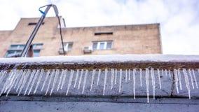 Wintereiszapfen als Zaun gegen mehrstöckiges Haus und Himmel mit weißen Wolken Hängende Eiszapfen des Winters auf dem Hausdach Lizenzfreie Stockbilder