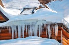 Wintereiszapfen, die am Landhausdach hängen Stockbilder