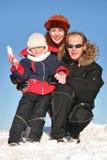 Winterfamilie sitzen auf Schnee Stockfotos