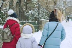 Winterfamilienweg in der Stadt, die Mutter und ihre Töchter gehen entlang die schneebedeckte Stadtstraße, die Ansicht von der Rüc Lizenzfreie Stockfotos