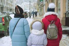Winterfamilienweg in der Stadt, die Mutter und ihre Töchter gehen entlang die schneebedeckte Stadtstraße, die Ansicht von der Rüc Stockfoto