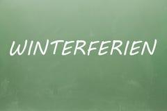 Winterferien écrit sur un tableau noir Photos stock