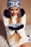 Winterfoto des netten kleinen Mädchens mit dem langen blonden Haar, das einen Hut und Handschuhe trägt Lizenzfreie Stockbilder