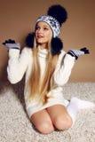 Winterfoto des netten kleinen Mädchens mit dem langen blonden Haar, das einen Hut und Handschuhe trägt Lizenzfreie Stockfotografie