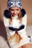 Winterfoto des netten kleinen Mädchens mit dem langen blonden Haar tragende ein Hut-ANG-Handschuhe, die Schneeball halten Stockfoto