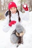 Winterfrau, die im Schnee spielt Stockbild