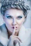 Winterfrau mit einem Finger über Mund stockfoto
