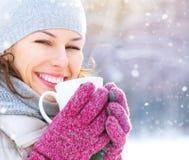 Winterfrau mit heißem Getränk draußen Stockfotografie