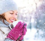 Winterfrau mit heißem Getränk draußen Stockbild