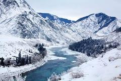 Wintergebirgsatemberaubende Landschaft, Türkisflussbetrieb zwischen den Berghängen, weißer Schnee, gezierter Wald stockfoto
