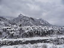 Wintergebirgsfluß und schöne Berge unter dem Schnee Stockfotos