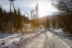 Wintergebirgslandschaftsstraße und bunte Blendenflecke Stockbilder