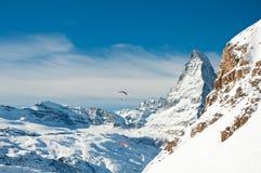 Wintergleitschirmfliegen über den Alpen Lizenzfreies Stockbild