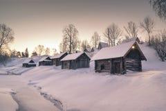 Winterhäuser auf Hügeldorf über gefrorenem Fluss Stockfoto