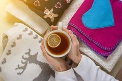 Winterhintergrund-Bildstapel der warmen woolen Kleidung auf Tabelle, eine Schale heißer Tee Stockfoto