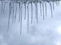 Winterhintergrund mit Eiszapfen und bewölktem Himmel lizenzfreies stockfoto