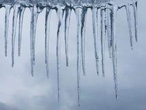 Winterhintergrund mit Eiszapfen und bewölktem Himmel stockbild