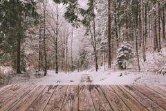 Winterhintergrund mit hölzernem Terrassen- und Naturwald gestalten landschaftlich Weihnachtsfeiertagskonzept Stockbild