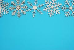 Winterhintergrund mit Schneeflocken Hölzerner Laser schnitt Schneeflocken auf die Oberseite auf blauem Hintergrund Lizenzfreie Stockfotos