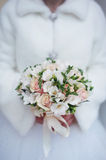 Winterhochzeitsblumenstrauß in den Händen der Braut Stockfoto