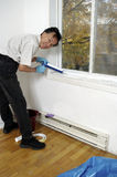 Home winter energy saving by applying window caulk Stock Photography
