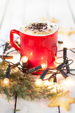 Winterkaffee in einem roten Becher mit Weihnachtslichtern und -plätzchen Stockfotografie