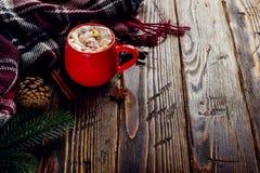 Winterkaffeegetränk, Kakao mit Schlagsahne und Eibische in einer roten keramischen Schale Stellung auf einem Holztisch, nahe bei  stockbilder
