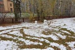 Winterkind-` s Unterhaltung am Weihnachten - Schneemänner vom ersten Schnee Stockfotografie