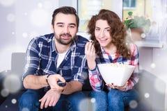 Winterkonzept - glückliches junges Paar, das zu Hause Fernsehen oder Film aufpasst Lizenzfreie Stockfotos