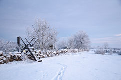 Winterland with a stile at a stone wall Royalty Free Stock Images