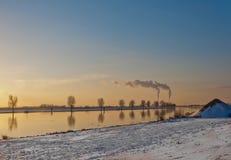 Winterlandscape con un fiume ed i camini di fumo fotografia stock