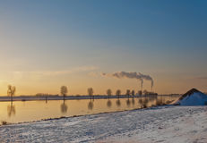 Winterlandscape with a river and smoking chimneys Stock Photo