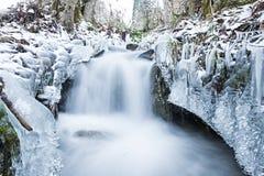 Winterlandschaft, die einen laufenden Nebenfluss des Wassers kennzeichnet Lizenzfreie Stockfotografie