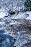 Winterlandschaft, Fluss unter dem Eis und dem Schnee und Baumaste umfasst mit Reif Lizenzfreie Stockfotos