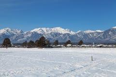 Winterlandschaft mit Ansichten der Berge und des kleinen Dorfs stockbilder