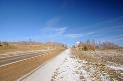 Winterlandschaft mit Asphaltstraße, bloßen Bäumen, erstem Schnee und UeberholverbotVerkehrsschild unter dunkelblauem Himmel stockbilder