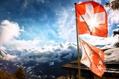 Winterlandschaft mit Bergspitzen und Schweizer Flagge lizenzfreie stockfotografie