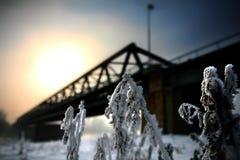 Winterlandschaft mit Brücke und Sonne im Hintergrund Lizenzfreies Stockbild