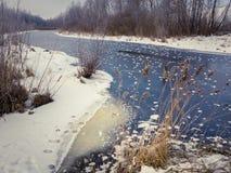 Winterlandschaft mit dem Fluss bedeckt mit Eis und Frost Lizenzfreie Stockbilder