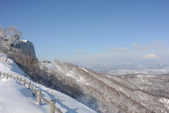 Winterlandschaft mit einem schneebedeckten Vulkan und einem Hotel Lizenzfreies Stockbild