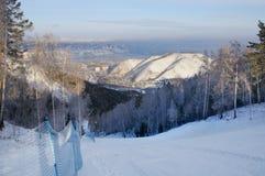 Winterlandschaft mit einer Skisteigung und eine Ansicht der Stadt von Krasnojarsk auf dem Horizont lizenzfreie stockfotografie